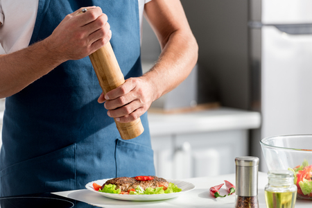 Cropped view of man salting steak with salt mill Stock Photo