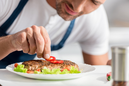 Close up view of adult man adding pepper to cooked steak