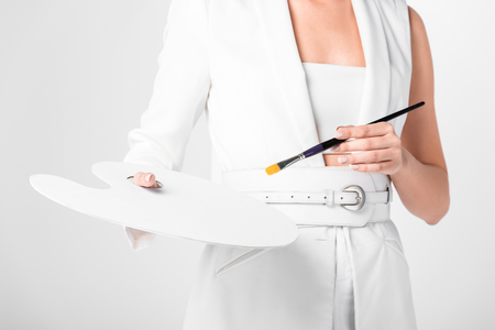 Female artist in total white posing with palette and paintbrush isolated on white Reklamní fotografie