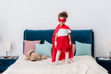 Smiling little african american child in superhero costume standing on bed with colourful pillows