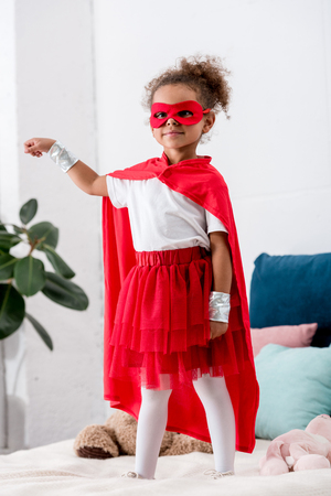 Cute little african american kid in red superhero costume gesturing while standing on bed Stock Photo
