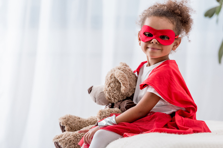 Adorable little african american kid in superhero costume and mask with teddy bear Stock Photo