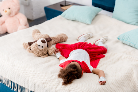 Little child in red superhero costume with teddy bear lying on bed Stock Photo