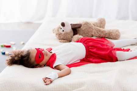 Cute little african american child in superhero costume and mask lying on bed with teddy bear Stock Photo
