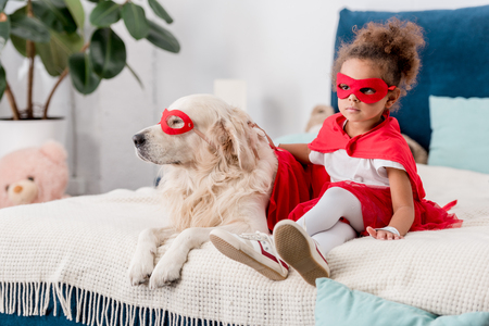 Adorable little african american kid with dog in superhero costumes sitting on bed Stock Photo