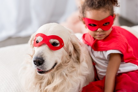 Adorable little african american kid with dog in superhero costumes and red masks