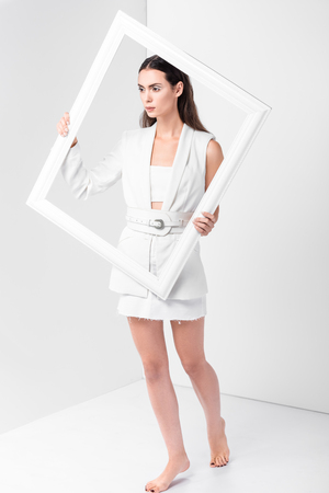 Beautiful barefoot woman in total white holding white frame