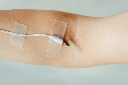 Close up of female hand with attached white cable  like medical IV infusion isolated on grey, music concept