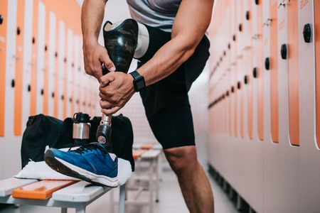 Cropped shot of sportsman putting on artificial leg at gym changing room Stock Photo