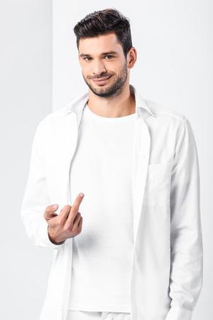 Adult handsome man showing middle finger on white background Reklamní fotografie