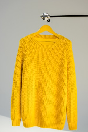 Knitted yellow sweater on hanger at grey background Archivio Fotografico - 112348016