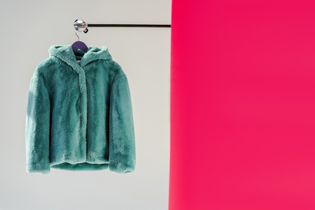 Close up of fluffy green faux fur coat on hanger with pink wallpaper