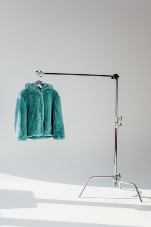 Fluffy green faux fur coat hanging on rack at grey background Foto de archivo - 112348065
