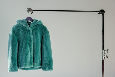 Fluffy green faux fur coat hanging on rack at grey background with sunbeams Stock Photo