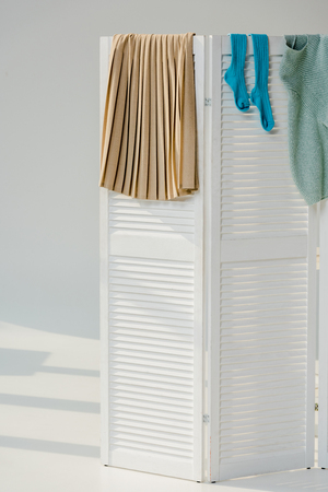 A multicolored female clothes hanging on white room divider