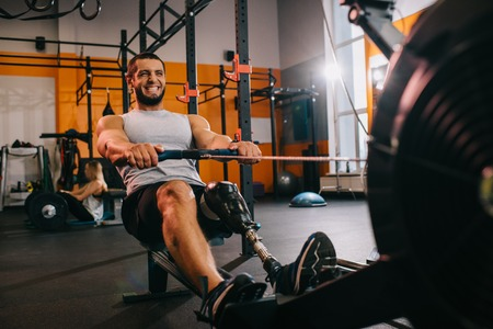 A handsome young sportsman with artificial leg working out with rowing machine at gym