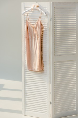 Silk nightie with lace hanging on white room divider