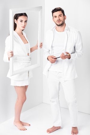 An attractive adult woman holding frame near barefoot man with paintbrush on white background