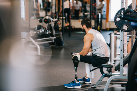 An overworked sportsman with artificial leg sitting at gym