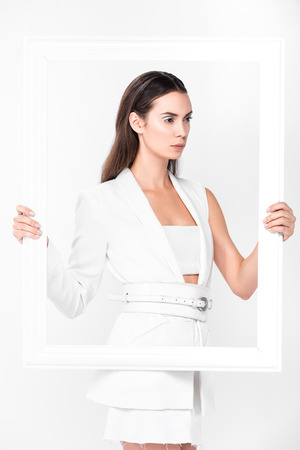 A beautiful woman in total white holding a frame isolated on white Reklamní fotografie