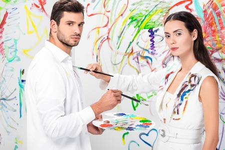 Studio shot of couple in total white drawing on clothes with paint brushes