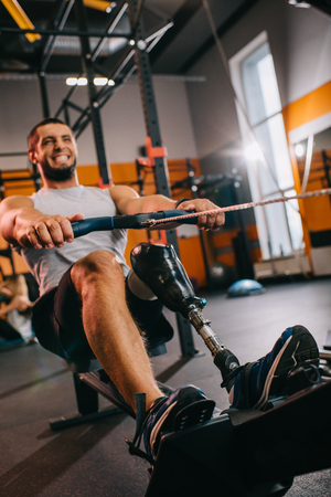 Muscular young sportsman with artificial leg working out with rowing machine at gym Stock fotó