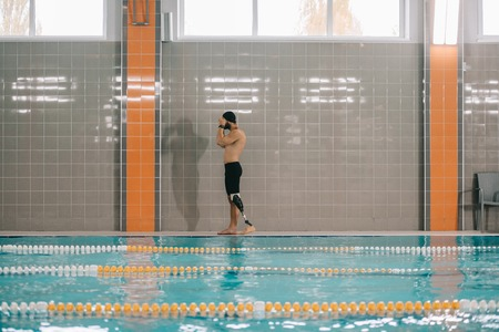 Handsome young sportsman with artificial leg standing on poolside at indoor swimming pool Stock Photo