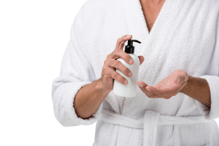 Cropped image of man in bathrobe using body lotion isolated on white