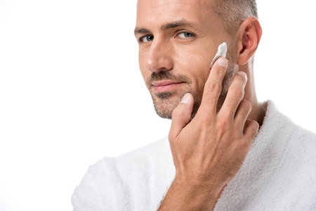 Adult handsome man in bathrobe applying beauty cream on face isolated on white