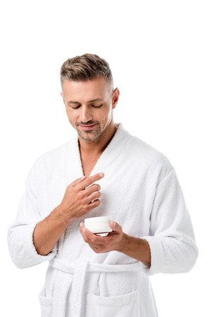 Man in bathrobe holding beauty cream on isolated on white