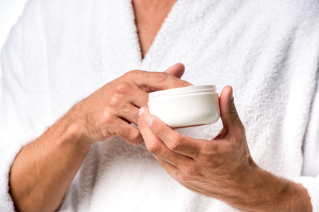Cropped image of man in bathrobe holding beauty cream isolated on white