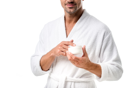 Partial view of man in bathrobe holding beauty cream isolated on white