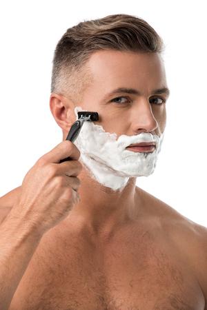 Fokussierter erwachsener Mann mit Schaum im Gesicht, der sich mit Rasiermesser isoliert auf Weiß rasiert