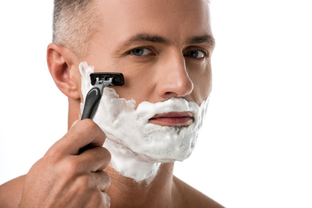 Close up portrait of man with foam on face shaving with razor isolated on white 写真素材