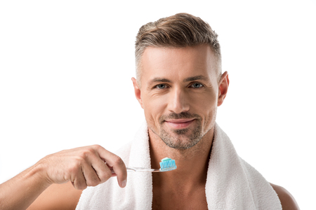 Portrait of adult man with toothbrush looking at camera isolated on white