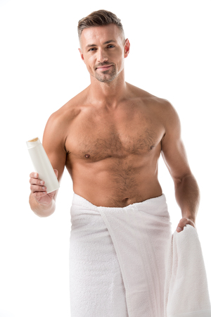 Happy adult man wrapped in towel holding shower gel isolated on white Stock Photo