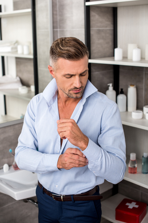 Confident adult businessman buttoning up blue shirt in bathroom at home