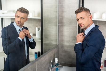 Vista de ángulo alto del empresario adulto ajustando la corbata delante del espejo en el baño.