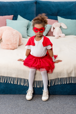 Cute little African american child in red superhero costume and mask sitting on the bed Stock Photo