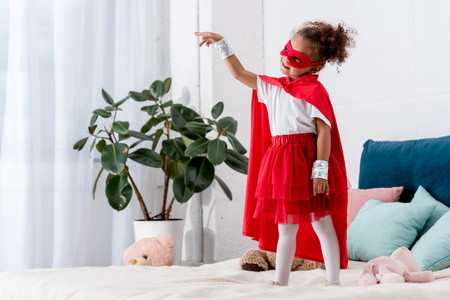 Adorable little African american child in red superhero costume gesturing while standing on bed