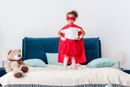 Little African american kid in red superhero costume and mask with hands on hips standing on bed
