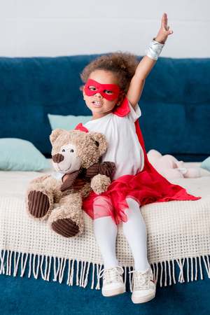 Adorable little African american child in superhero costume sitting on bed with teddy bear Banco de Imagens