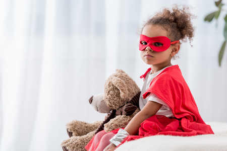 Cute African american child in red superhero costume and mask with teddy bear looking at camera