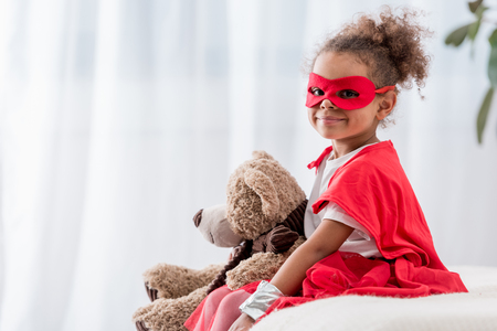 Adorable little African american child in superhero costume and mask with teddy bear smiling at camera Stock Photo
