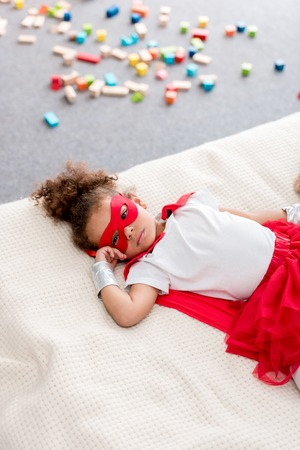 Cute little African american child in red superhero costume and red mask lying on bed