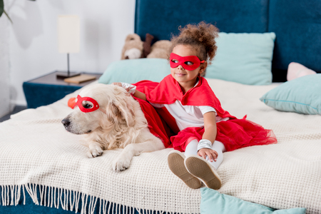 Cute little African american kid with dog in red superhero costumes sitting on bed Stock Photo