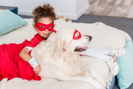 Cute little African american kid with dog in red superhero costumes lying on bed Banco de Imagens