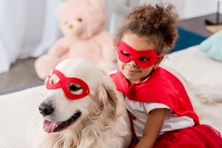 Smiling adorable little african american kid with happy dog in red superhero mask