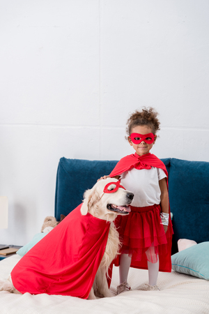 Cute little african american kid with happy dog in red superhero costumes standing on the bed Stock Photo