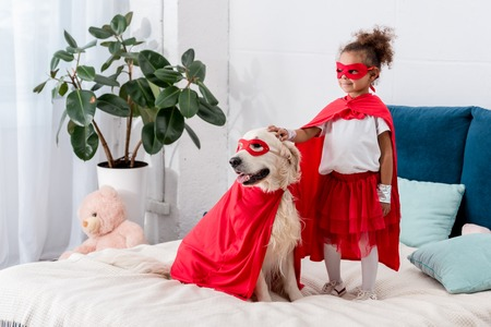Cute little african american kid with dog in superhero costumes looking away while standing on the bed